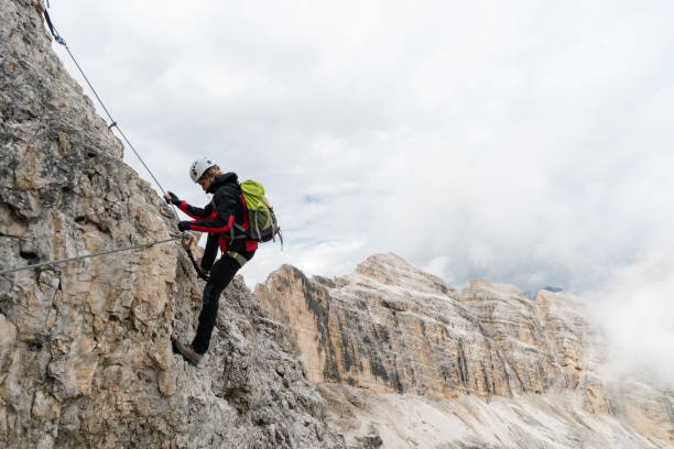 young female climber on a steep and exposed rock face climbing a Via Ferrata young attractive female university student on a steep and exposed rock face climbs a Via Ferrata in Alta Badia in the South Tyrol trentino alto adige stock pictures, royalty-free photos & images