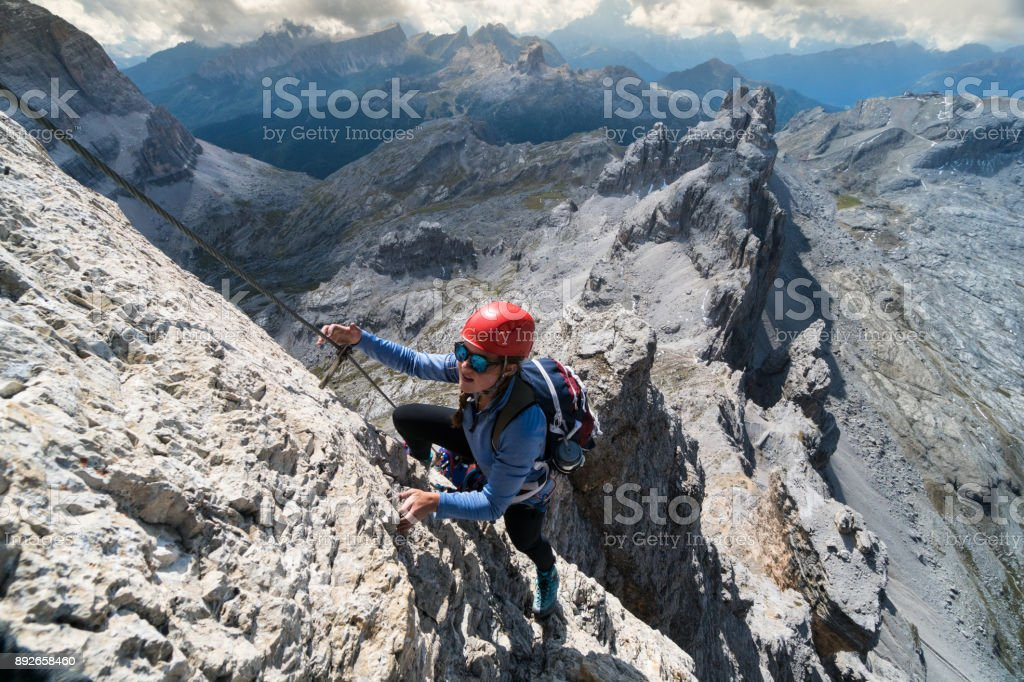young female climber on a steep Via Ferrata in Italy stock photo