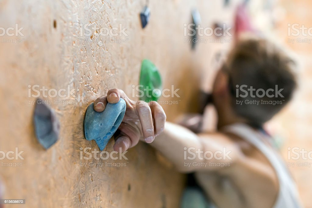 Young Female Climber on wall of indoor climbing gym stock photo