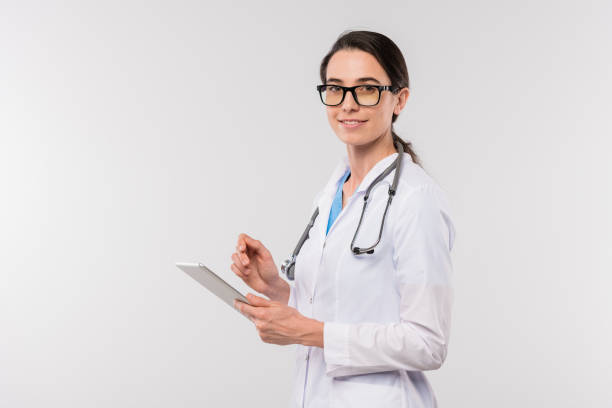Young female clinician in whitecoat and eyeglasses using touchpad in isolation stock photo