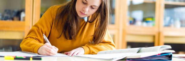 Junge weibliche College-Student im Chemieunterricht, Notizen schreiben. Fokussierte Schüler im Klassenzimmer. Authentische Bildungskonzept. – Foto