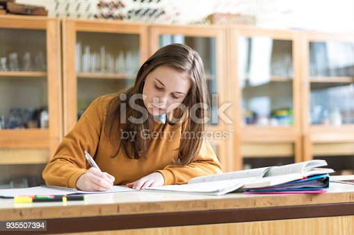 istock Young female college student in chemistry class, writing notes. Focused student in classroom. Authentic Education concept. 935507394