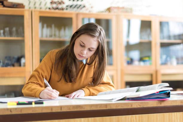 giovane studentessa universitaria in chimica, che scrive note. studente concentrato in classe. concetto di educazione autentica. - esame università foto e immagini stock