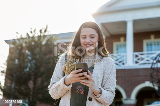 In this low angle view, a cheerful young female college student stands outdoors on her college campus.  She looks down at her smart phone as she texts.