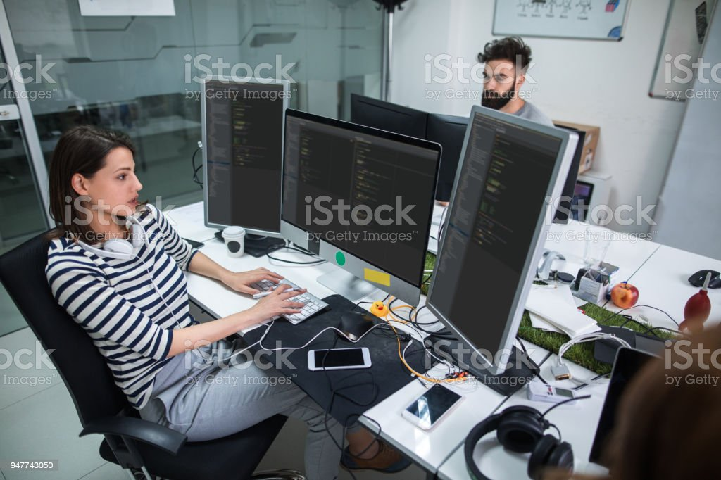 Young female computer programmer working on computer stock photo