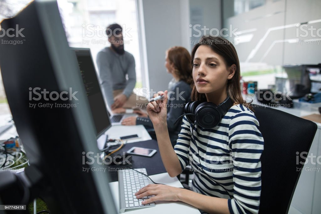 Young female computer programmer working on computer.