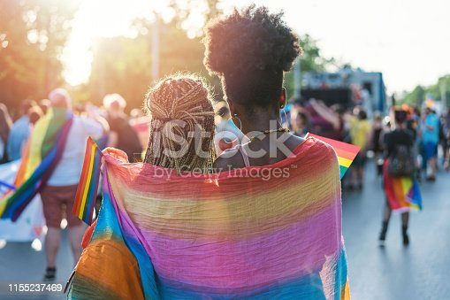 istock Young female couple hugging with rainbow scarf at the pride event 1155237469