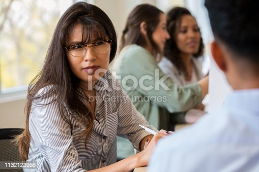 A serious young female creative professional sits at a conference table during a staff meeting next to an unrecognizable coworker.  She frowns in disbelief as she listens to him.