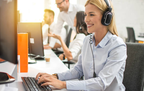 Young female customer service executive in headset working on computer in call center stock photo