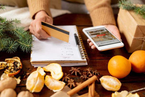 young female customer with credit card and smartphone going to order xmas gifts - shironosov stock pictures, royalty-free photos & images