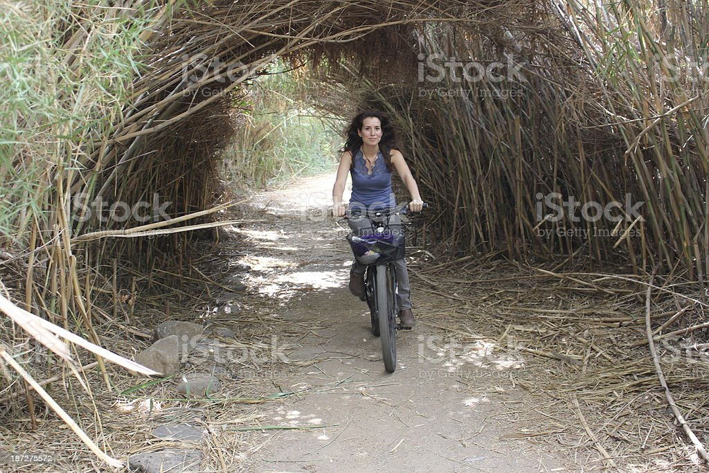 Young female cycling along nature path stock photo