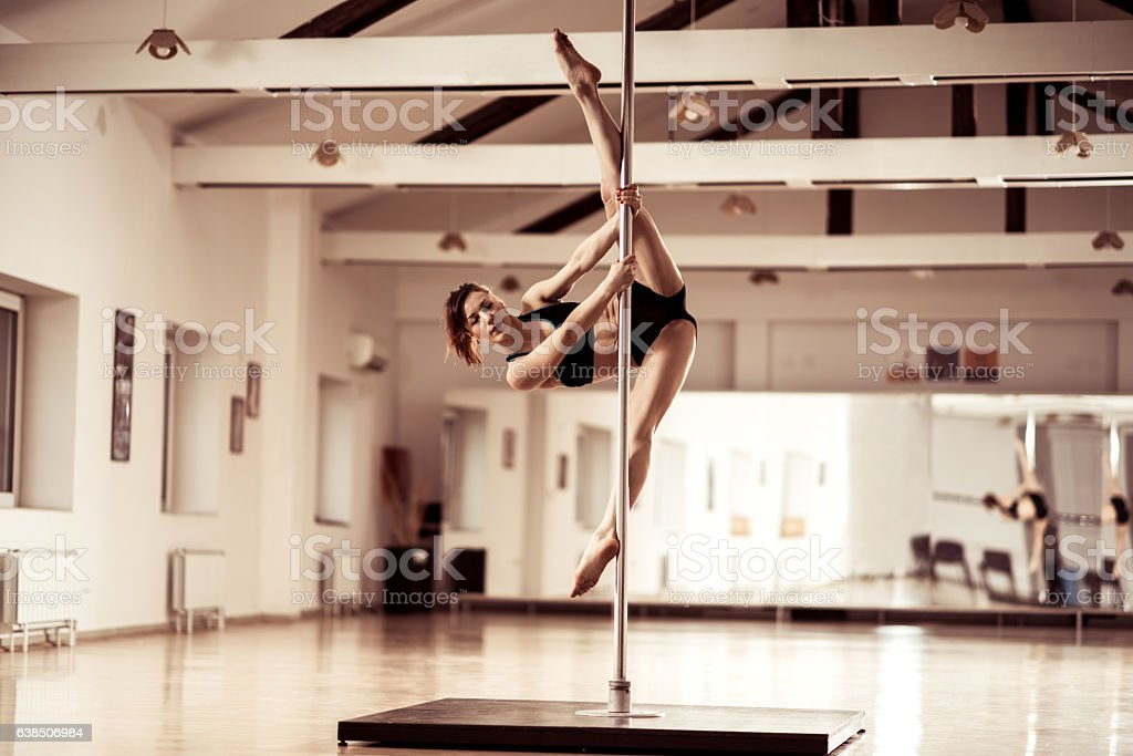 Young female dancer exercising extended frodo on a pole. stock photo