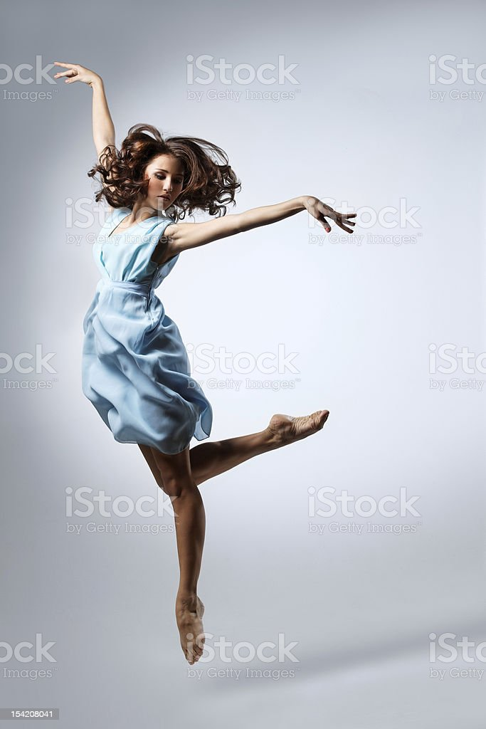 Young female dancer in a blue dress leaping in the air royalty-free stock photo