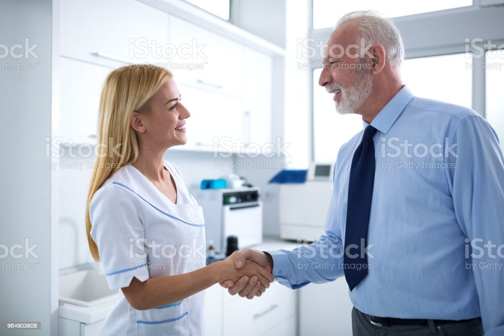 Young female dentist and patient are shaking hands royalty-free stock photo