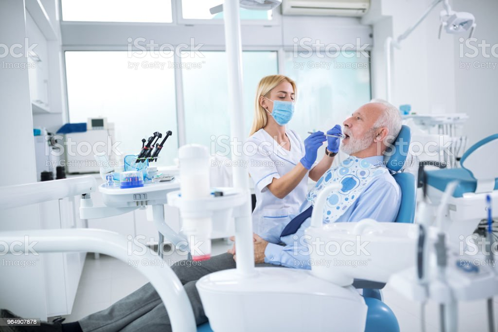 A young female dentist controls health of the tooth royalty-free stock photo