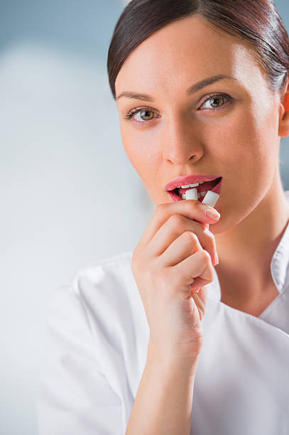 Young female dentist doctor holding chewing gum and smiling. stock photo