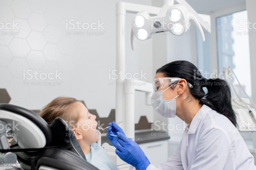 Junge Zahnärztin wird mündliche Überprüfung der Mundhöhle von kleinen Patienten zu tun - Lizenzfrei Arbeiten Stock-Foto