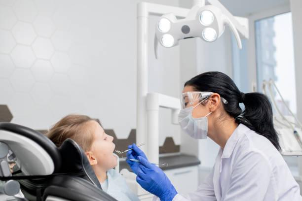 Joven odontóloga va a hacer chequeo oral de la cavidad oral de la pequeña paciente - foto de stock