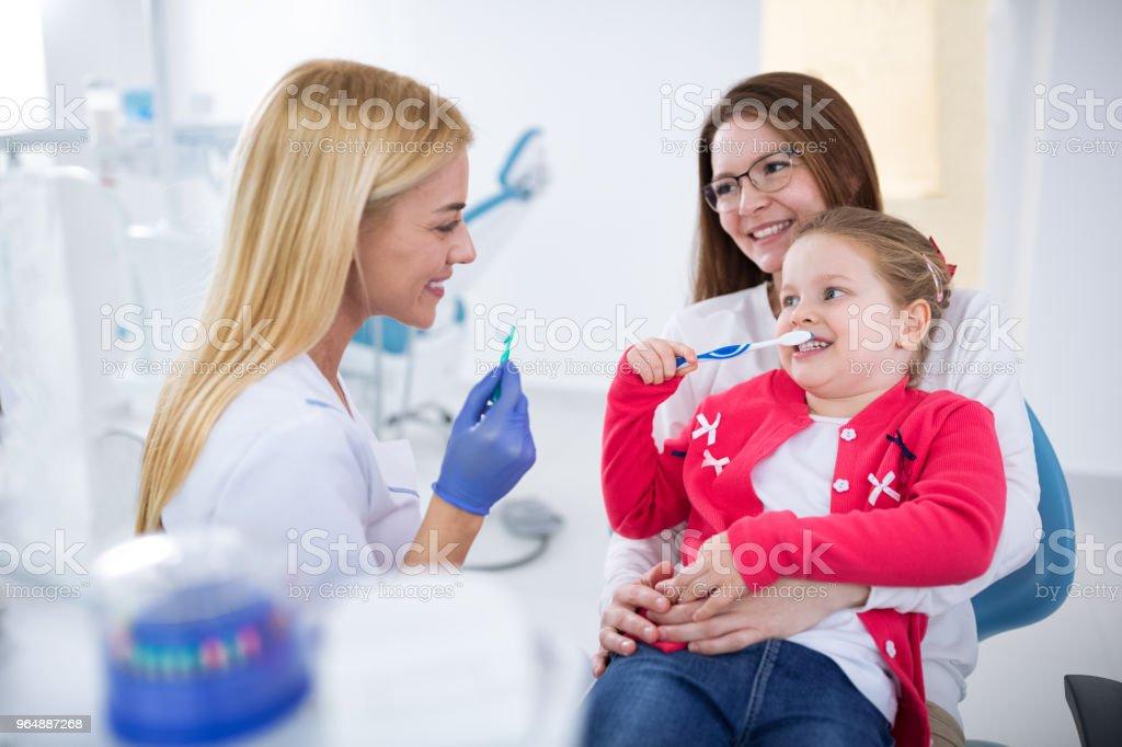 年輕女牙醫展示如何洗牙 - 免版稅一起圖庫照片