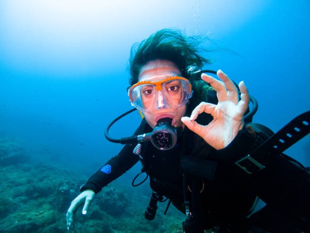 A young female diver making OK sign underwater looking at the camera stock photo