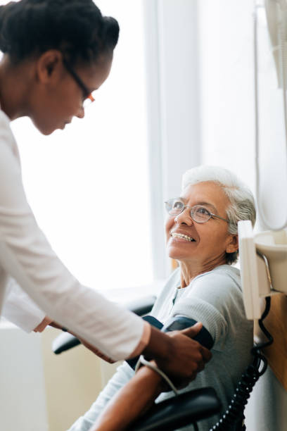 Young female doctor checking blood pressure of senior patient stock photo
