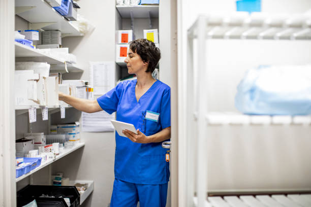 Young female doctor doing a medical supplies inventory in a hospital closet stock photo