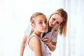 istock Young female doctor examining a small girl in her office. 926078478