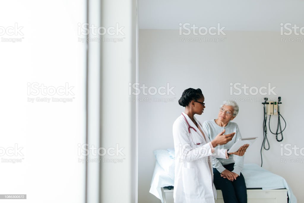 Young female doctor explaining patient with digital tablet A young female doctor explaining to a senior female patient using a digital tablet in a hospital room. 20-29 Years Stock Photo