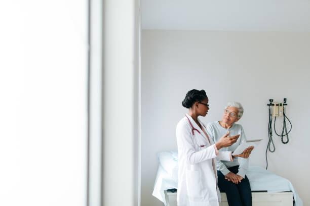 年輕女醫生解釋病人與數位片劑 - doctor patient 個照片及圖片檔