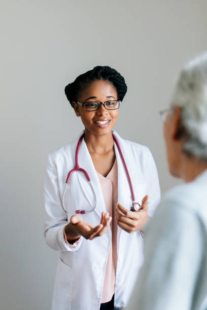 Young female doctor explaining senior patient A young female doctor wearing a lab coat, explaining to a senior patient, looking at each other and smiling. general military rank stock pictures, royalty-free photos & images
