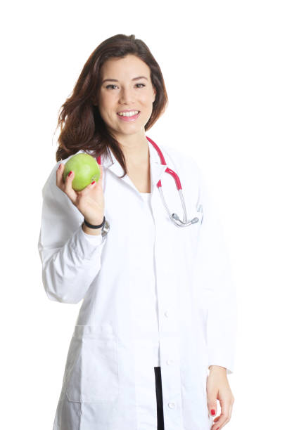young female doctor holding a green apple stock photo