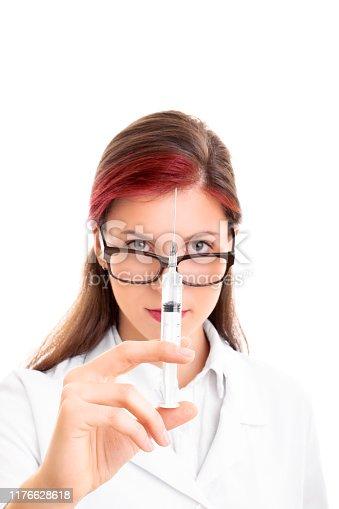 140378701istockphoto Young female doctor holding a syringe and needle 1176628618