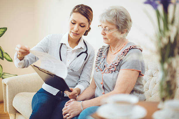 Young female doctor is consulting a senior patient stock photo