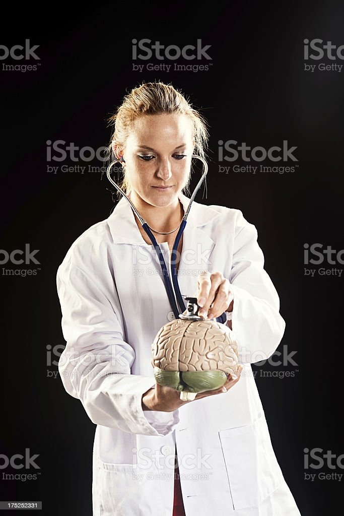 Young female doctor listens to model brain with stethoscope stock photo