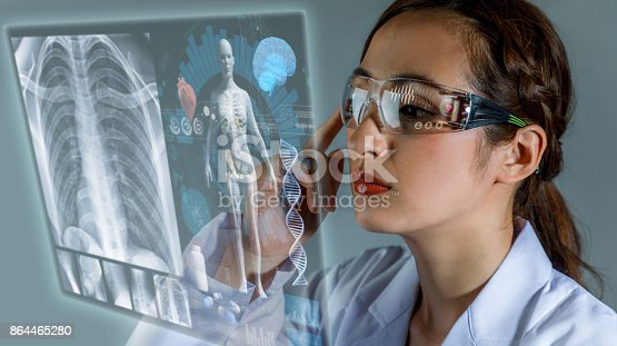 istock Young female doctor looking at hologram screen. Electronic medical record. Smart glasses. Medical technology concept. 864465280