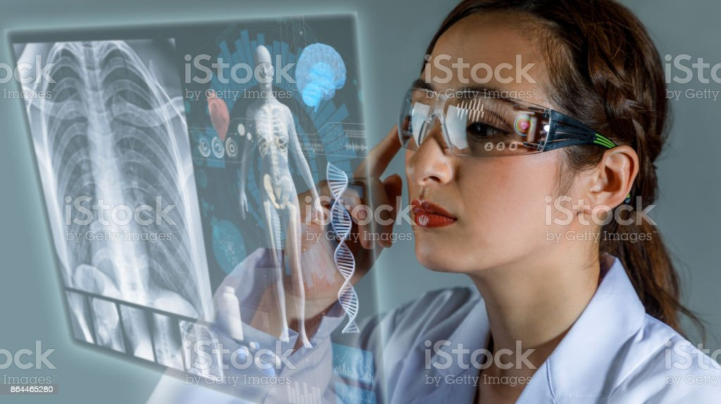 Young female doctor looking at hologram screen. Electronic medical record. Smart glasses. Medical technology concept. stock photo