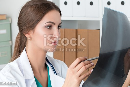 istock Young female doctor looking at lungs x-ray image 503221876