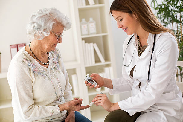 young female doctor making diabetes blood test on senior woman - diabetic stock photos and pictures