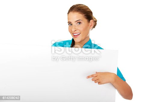 istock Young female doctor or nurse holding empty banner 614209242