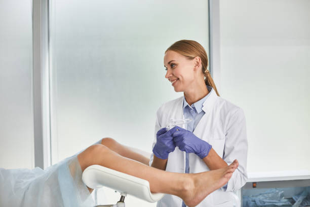 Young female doctor preparing for gynecological examination Waist up portrait of gynecologist in white lab coat and sterile gloves holding medical vaginal speculum. She is looking at patient and smiling gynecologist stock pictures, royalty-free photos & images
