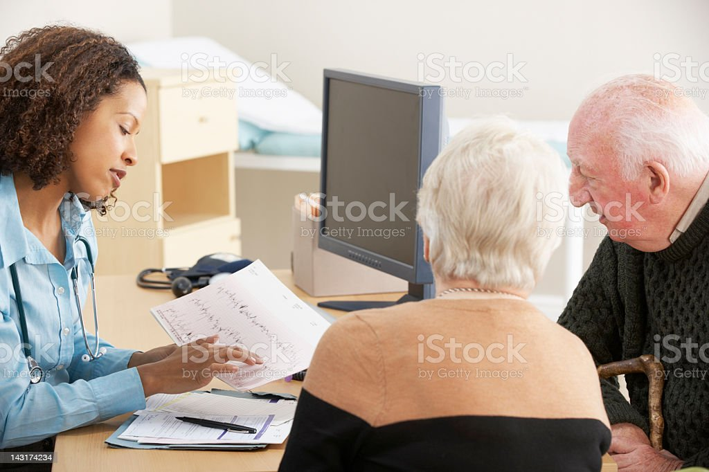 Young female Doctor talking to senior couple stock photo