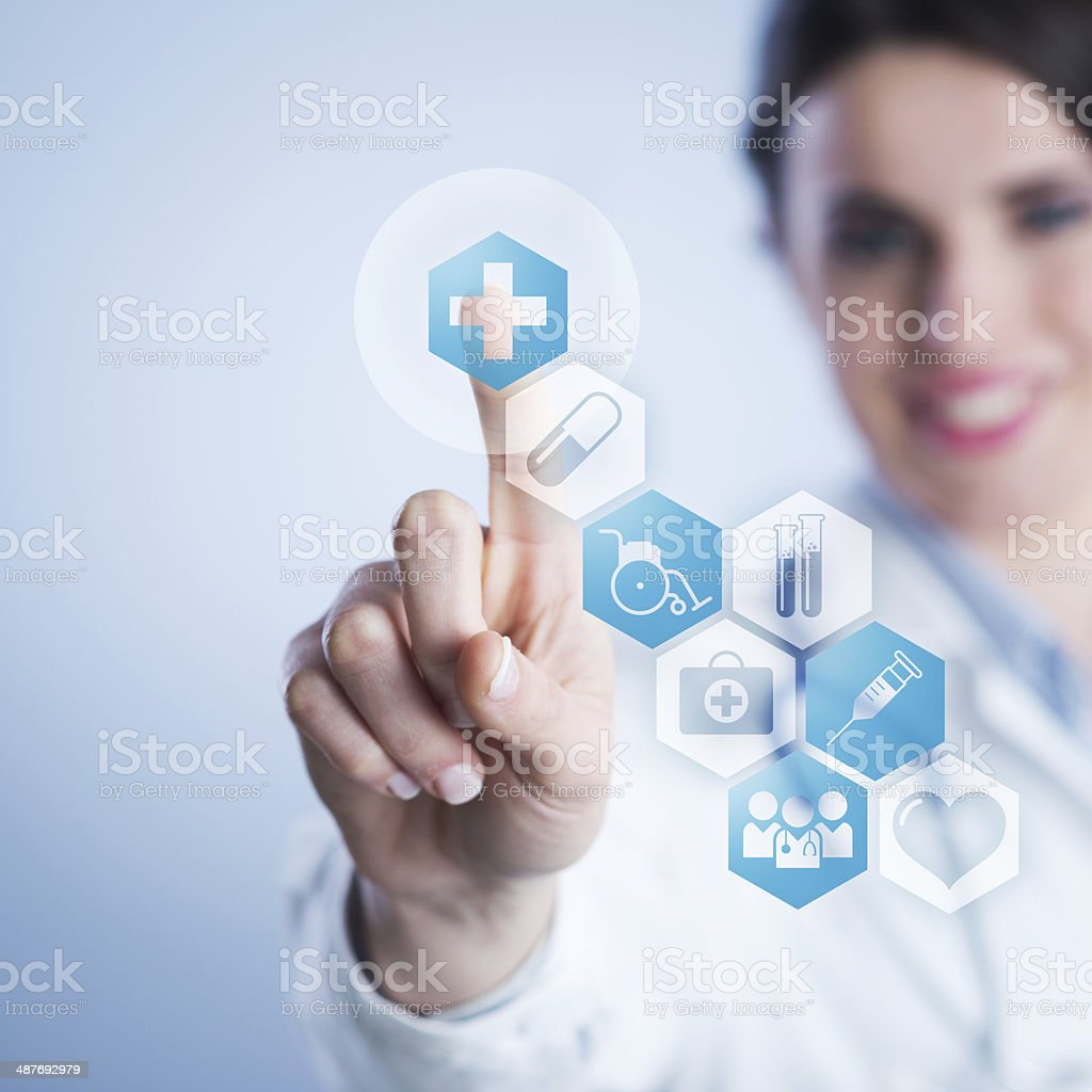 Young female doctor using touch screen interface. stock photo