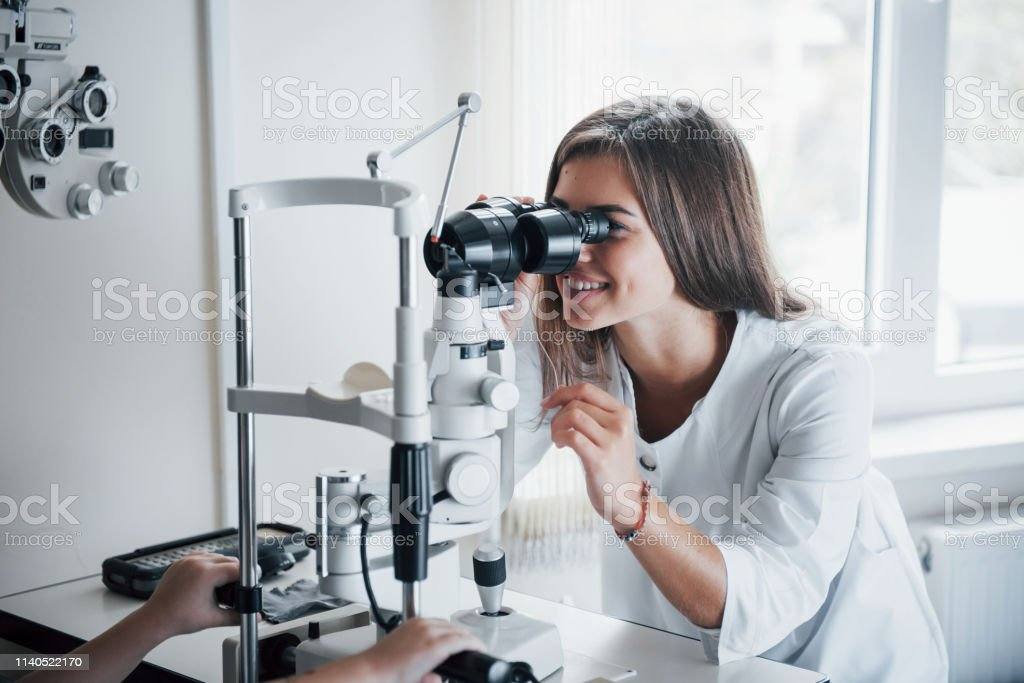 Young female doctor working with the eye testing equipment and...