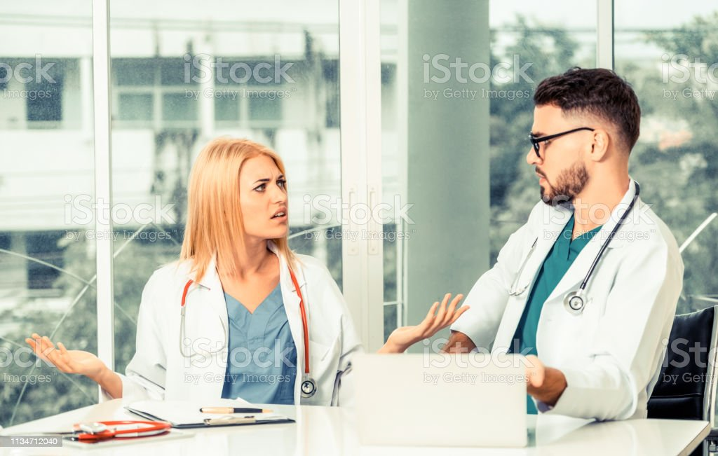 Young female doctor works at office in hospital while talking to male doctor sitting beside her. Medical service and healthcare concept. stock photo