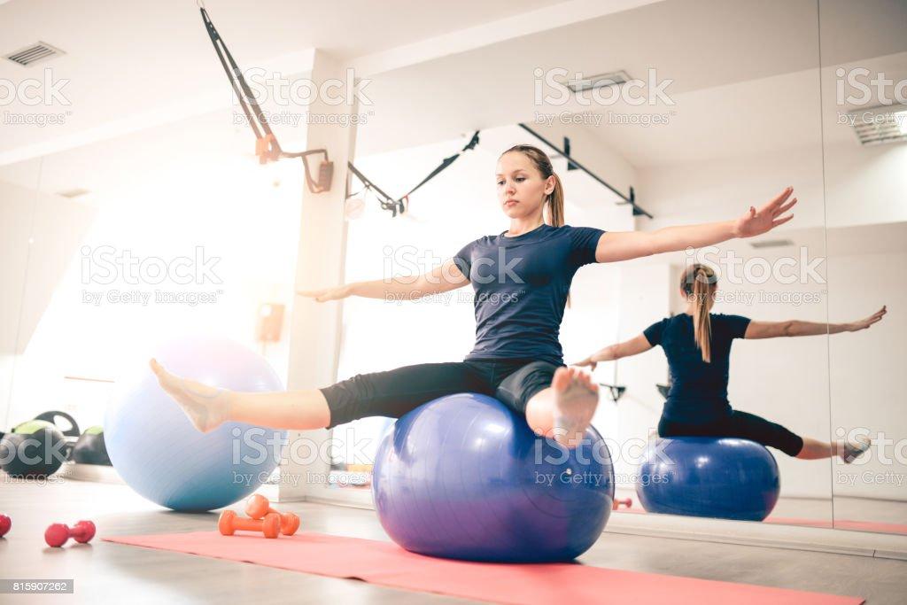 Mujer joven haciendo equilibrio Pilates ejercicio en pelota Fitness en  gimnasio foto de stock libre de 6dc33cd73adb