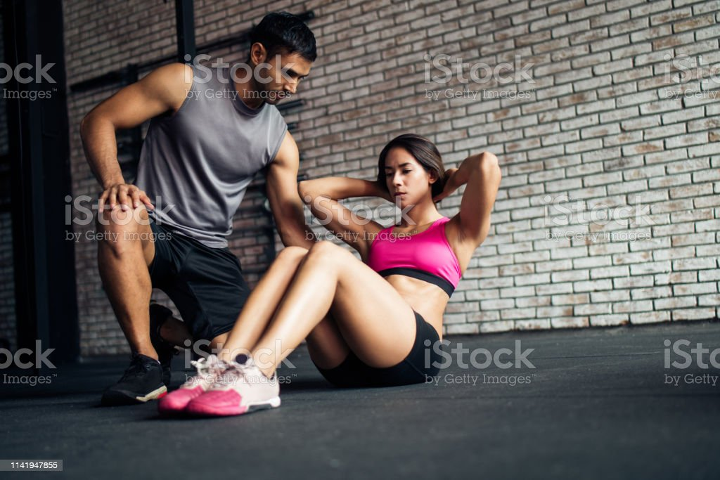 Young Female Doing Crunches On A Gym Floor Assisted By A Male