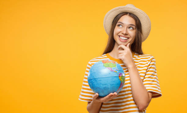 年輕的女性夢想著未來的旅行, 用一隻手拿著地球儀, 被孤立在黃色的背景上。旅行理念。 - future 個照片及圖片檔