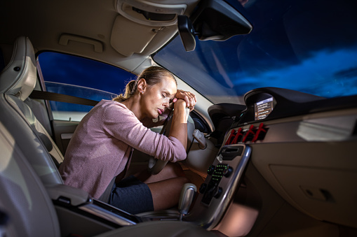 istock Young female driver at the wheel of her car, super tired 1179512830