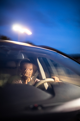 istock Young female driver at the wheel of her car, super tired 1179512841