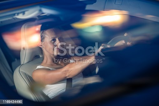 istock Young female driver driving her car at night 1169434490